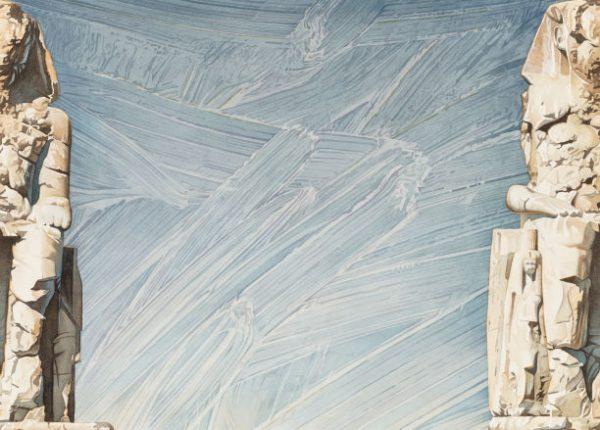 Blauer Himmel im Hintergrund mit zwei beigefarbenen Statuen links und rechts