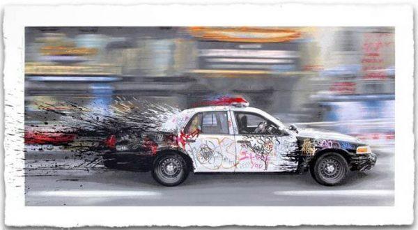 Bild eines vorbeibrausenden, farbverschmierten Polizeiautos, das eine Farbspritzer hinterherzieht