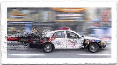 Bild eines vorbeibrausenden, farbverschmierten Polizeiautos.