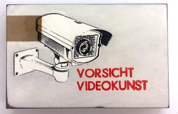 Bild einer Kamera im Comicstil, untertitelt mit