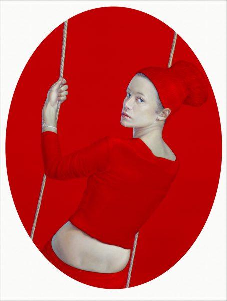 In rot gekleidete Frau auf Schaukel vor rotem Hintergrund